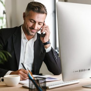 Image of handsome businessman 30s wearing suit talking on cell phone while working on computer in office